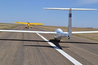 A glider takes off on an airport runway
