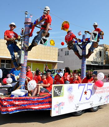 People ride on a float during a parade