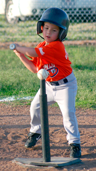 A child swings a bat at a baseball