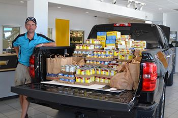 A man stands next to a truck filled with food