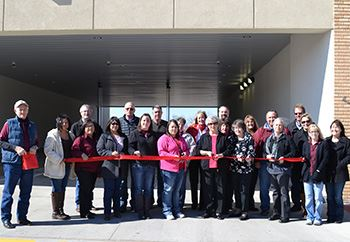 People gather for a ribbon cutting at a local business